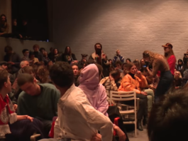 Een boze student die haar gezicht bedekt neemt het woord.